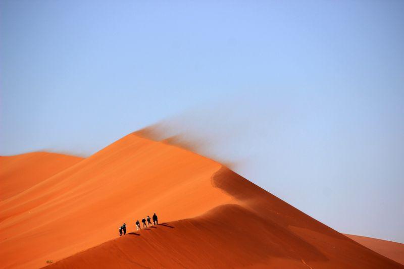 Photo of People Hiking Up Sand Dune