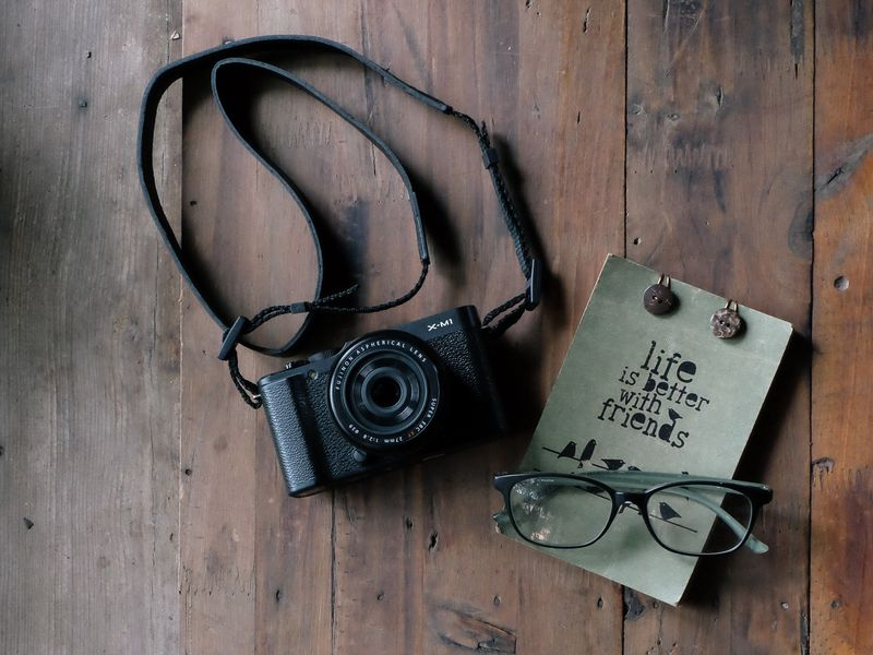 Photo of Camera, Glasses, and Notebook