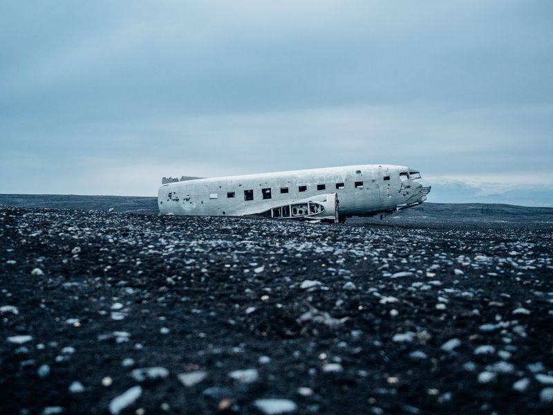 Photo of Crashed DC-3 Airplane on a Black Beach
