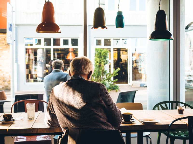 Photo of Man Sitting at Coffee Shop Table