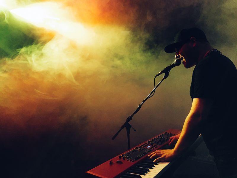 Photo of Man Playing Keyboard in Smoky Room