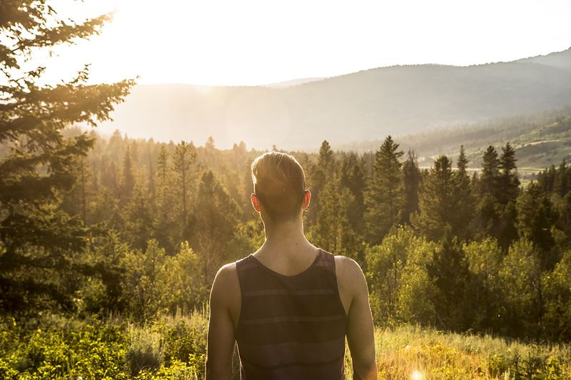 Photo of Man Looking at Hills and Forests