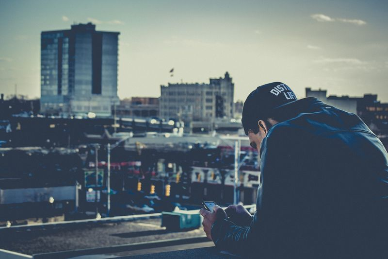 Photo of Man Texting on Roof