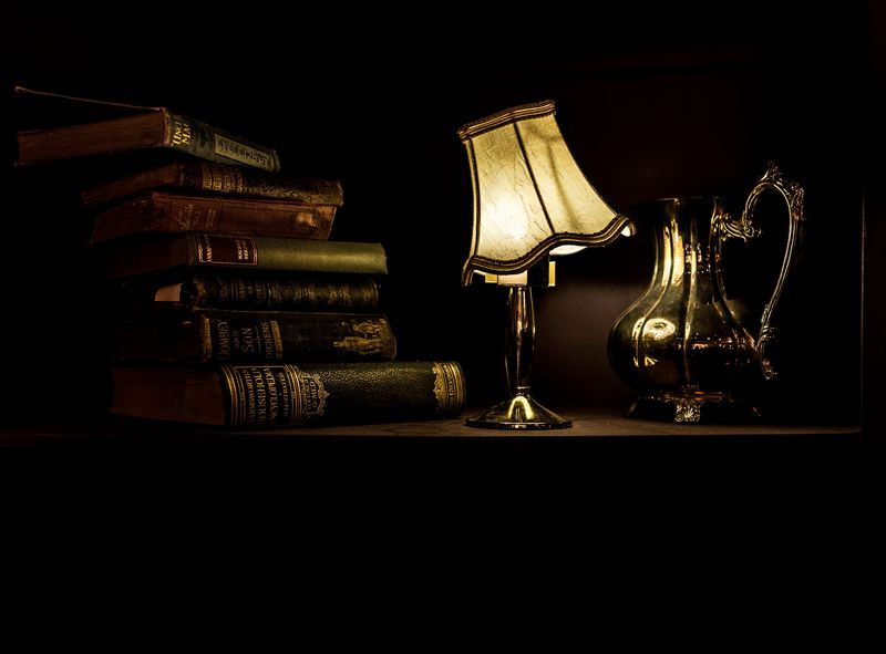 Photo of Books, a Lamp, and a Pitcher