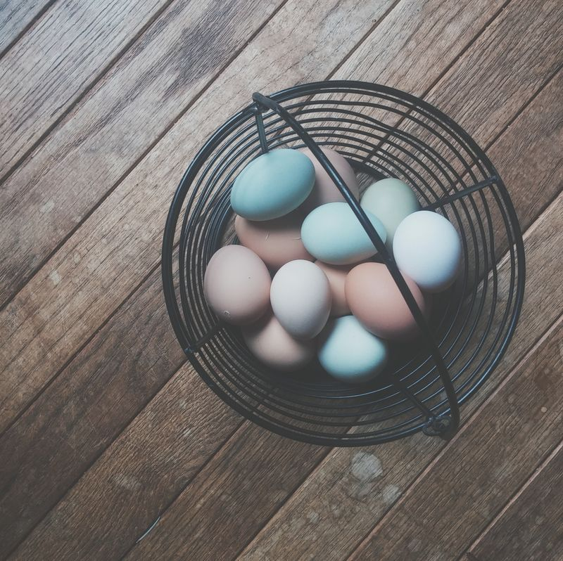 Photo of Eggs in a Basket on a Wooden Table