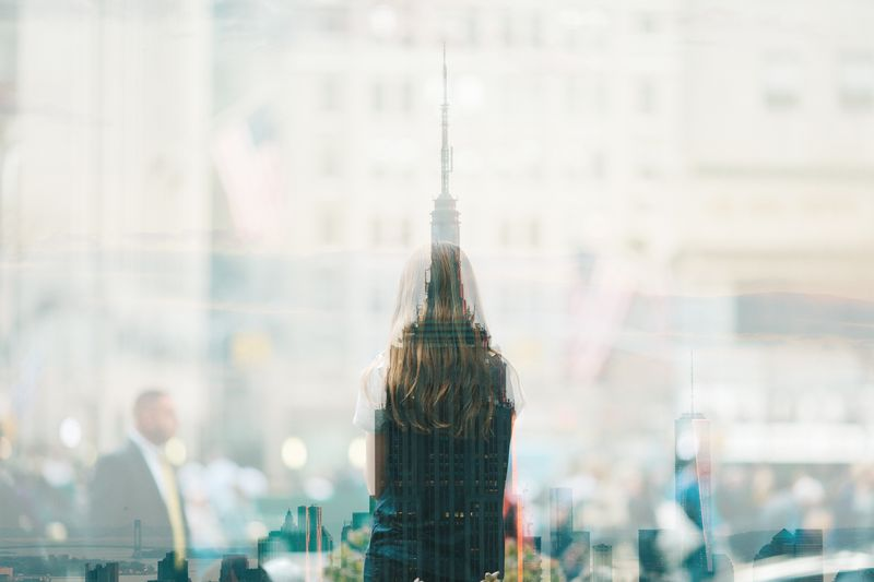 Photo of Woman through Glass and Reflection of Building