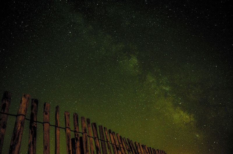 Photo of Wooden Fence under Starry Green Sky
