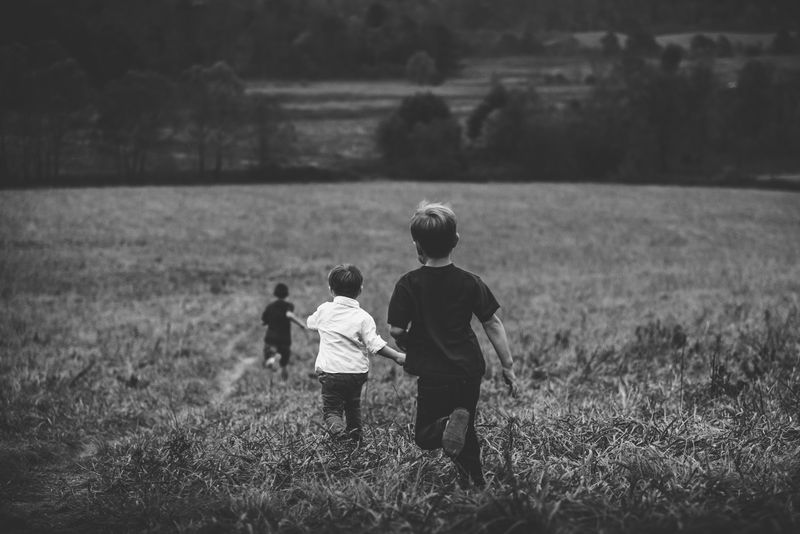 Photo of Children Running Through a Field