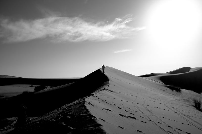 Photo of Person Walking in Desert