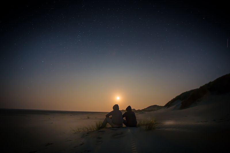 Photo of Two People Sitting in Sand