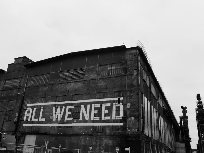 """Photo of """"All We Need"""" Written on an Old Steel Mill Building"""