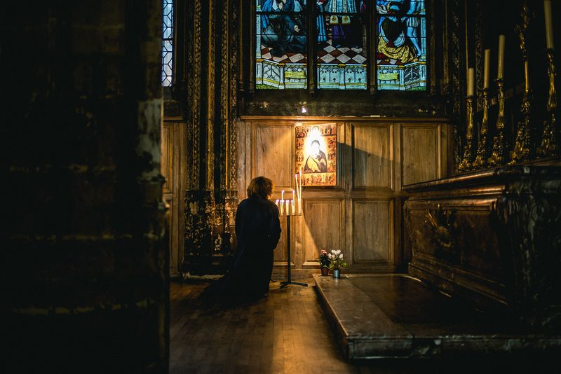 Photo of Woman Lighting Candle in Historic Church