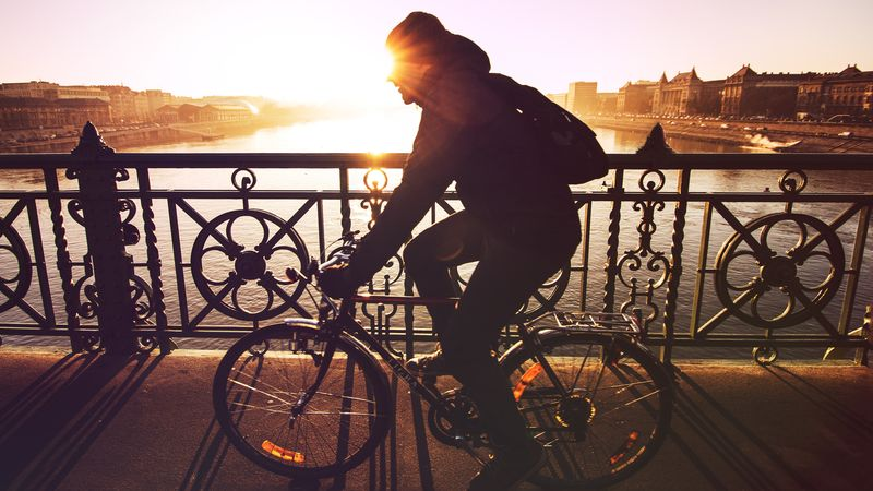 Photo of Man Riding Bicycle on River Bridge