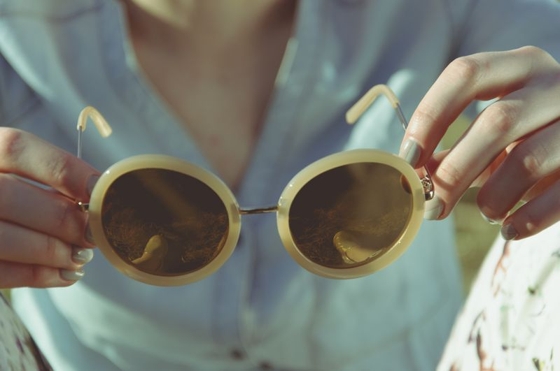 Photo of Woman Holding Sunglasses