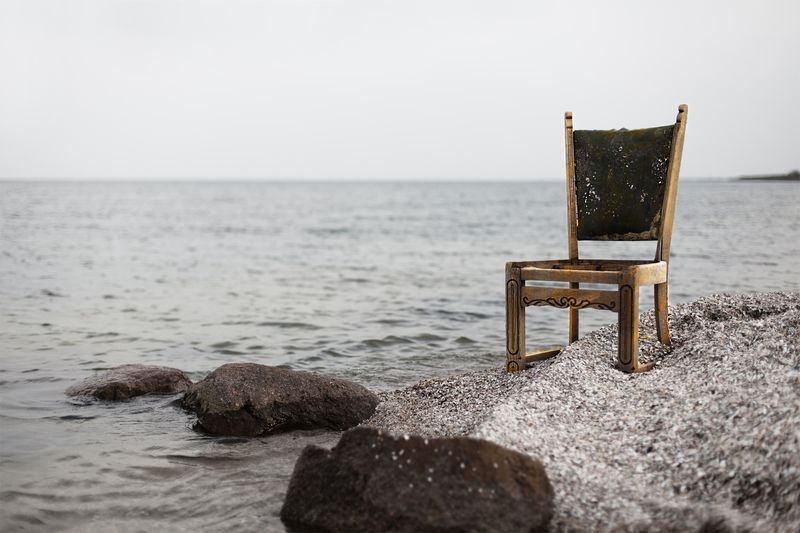Photo of Wooden Chair on Sandy Seashore