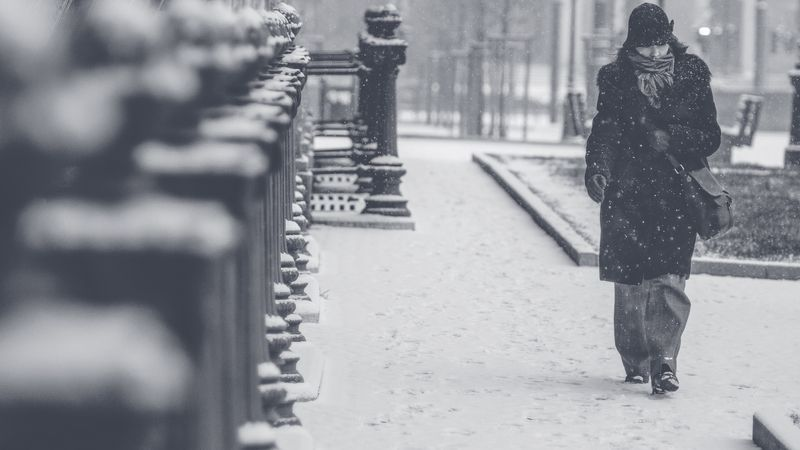 Photo of Woman Walking in Snowy City