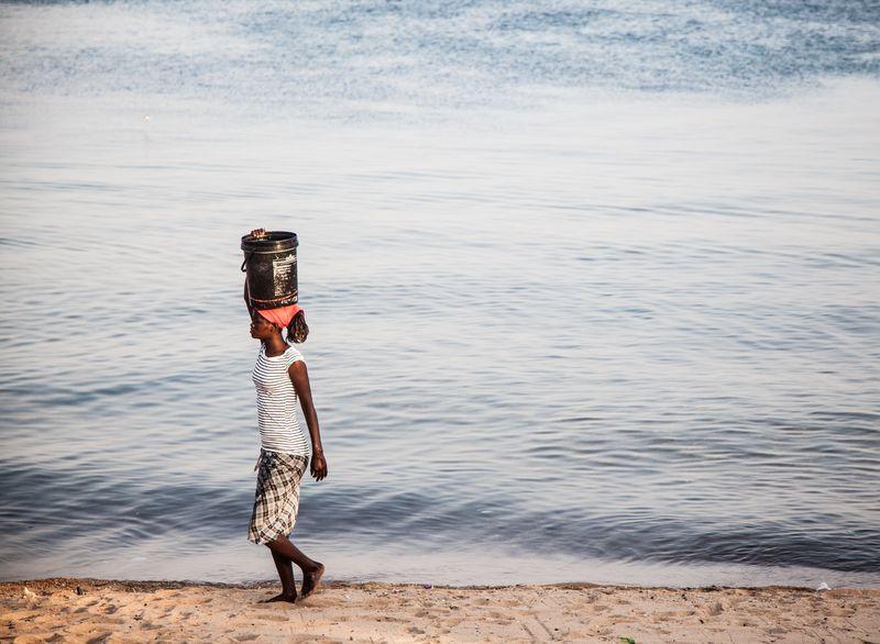 Photo of Woman Walking Along Beach Carrying Bucket