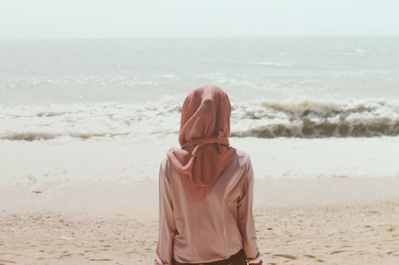 Photo of Woman with Headcovering Looking at Ocean