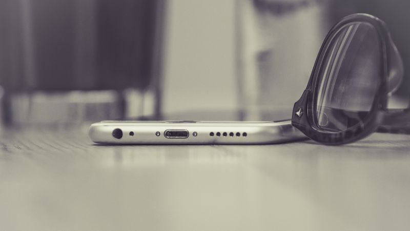 Photo of iPhone and Eyeglasses on Table
