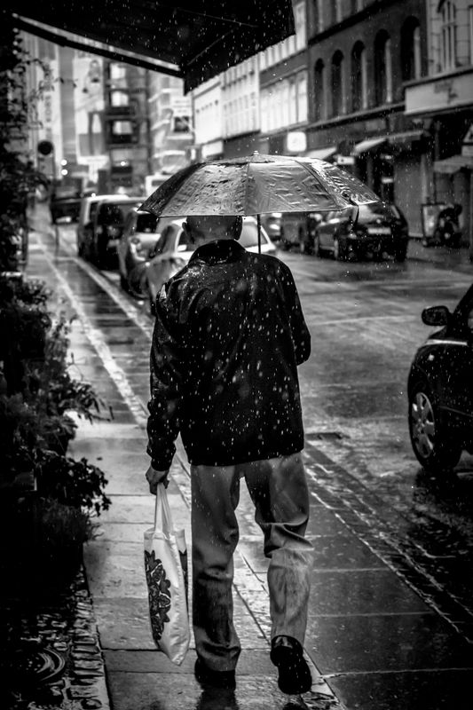 Photo of Man with Umbrella in Rain