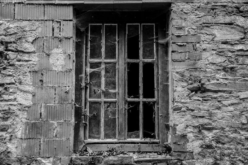 Photo of Dilapidated Window on Stone Building