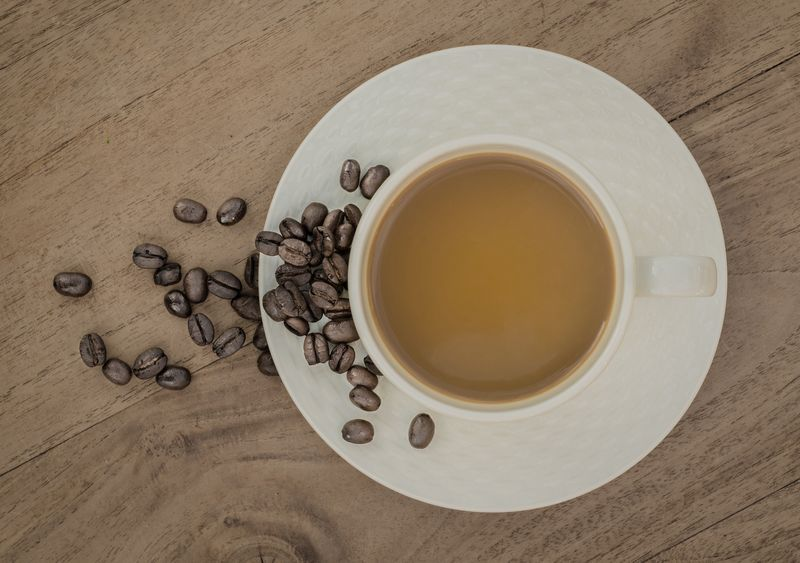 Photo of Cup of Coffee and Coffee Beans