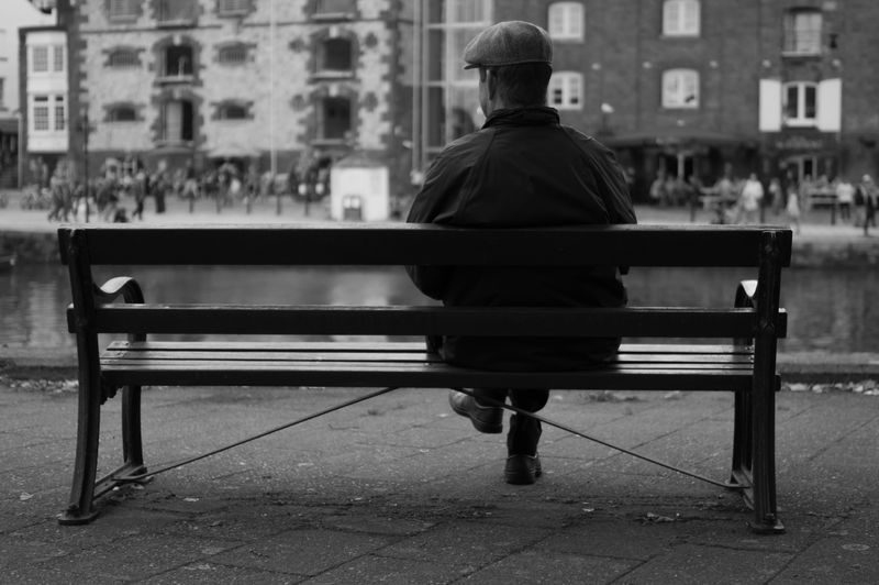 Photo of Man Sitting on City Bench
