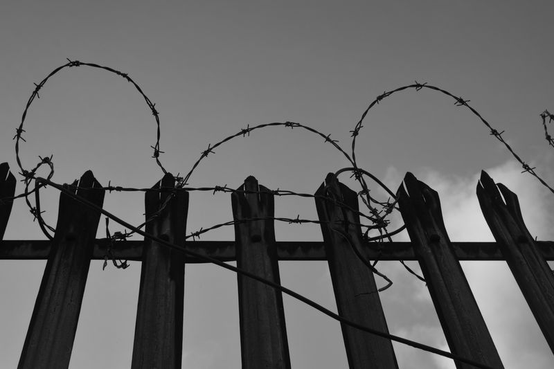 Photo of Barbed Wire on Top of a Metal Fence
