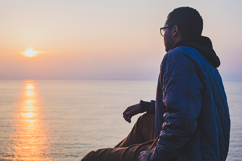 Photo of Man Looking at Sunset