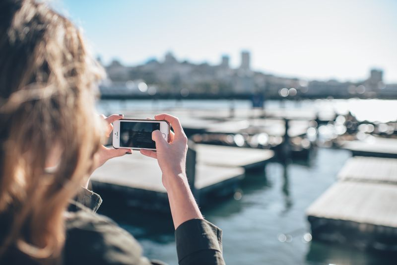 Photo of Woman Taking Photo of City