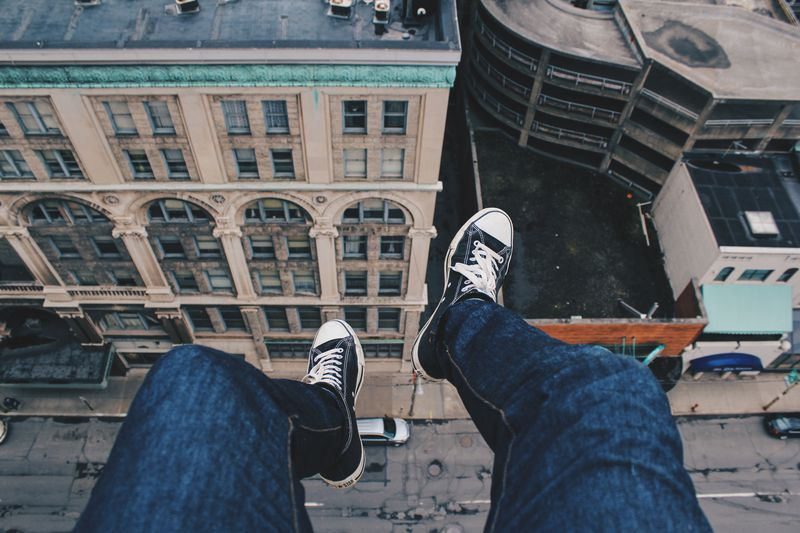 Photo of Feet Hanging Off Building over City Street