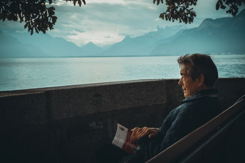 Photo of Elderly Man Sitting by Mountains and Sea